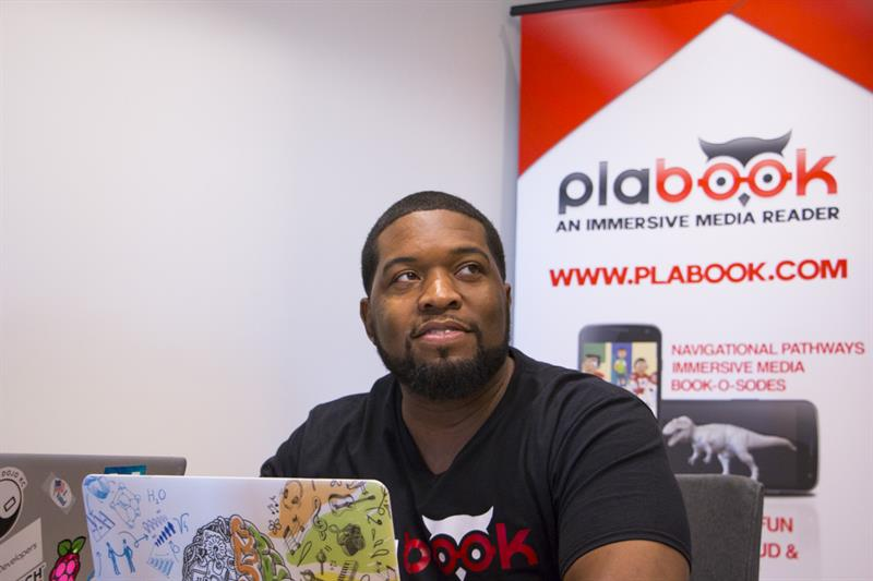 Philip Hickman of Plabook discusses work with a coworker in his office space