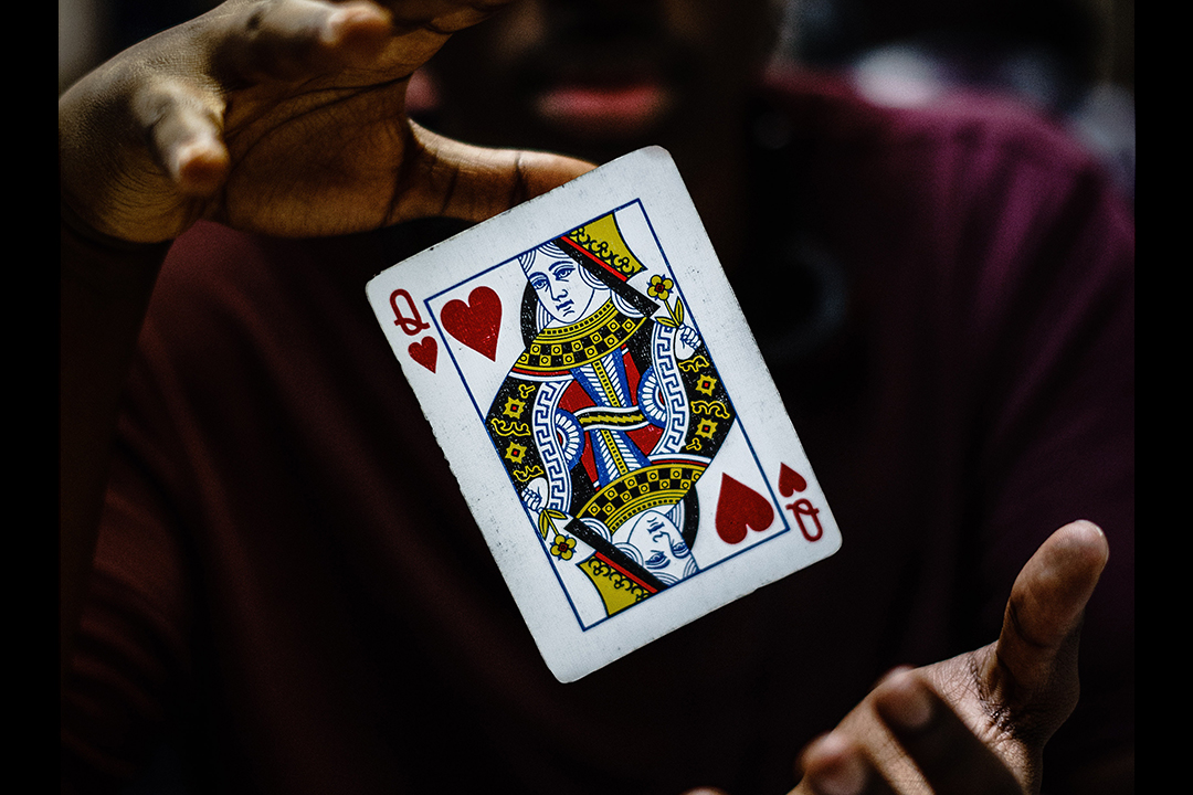 A playing card hovers between two hands