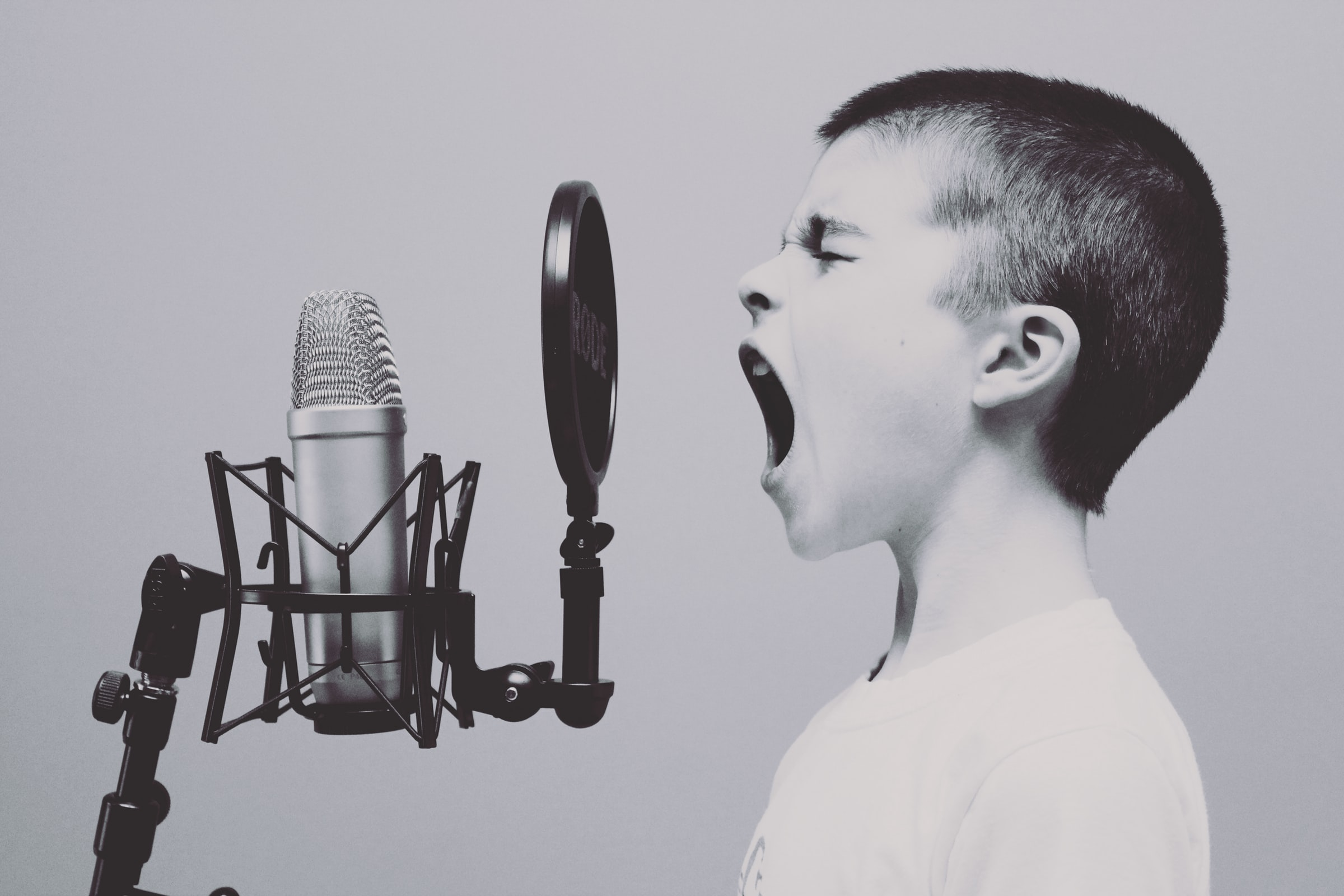 A boy yells into a pop filter and microphone