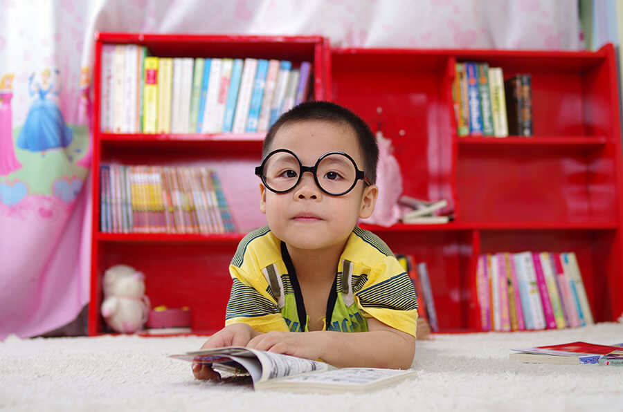 young boy with glasses reads a book at the library