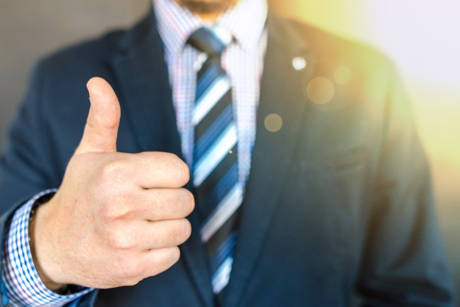 Man in suit gives a thumbs up