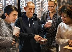 four people look at a smartphone