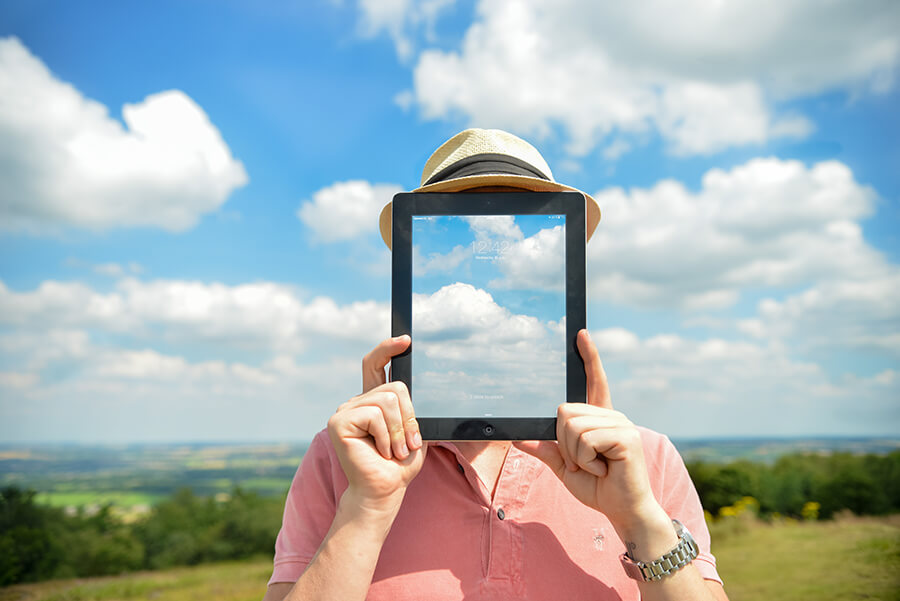 man holds tablet showing clouds in front of his face