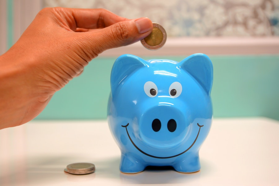 A hand puts coins into a blue piggy bank