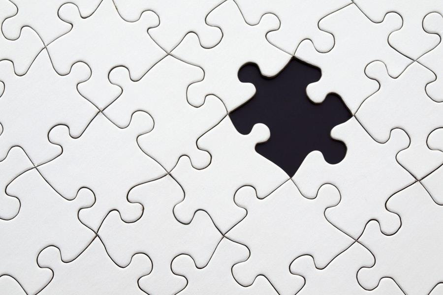 A missing puzzle piece among a completed white puzzle