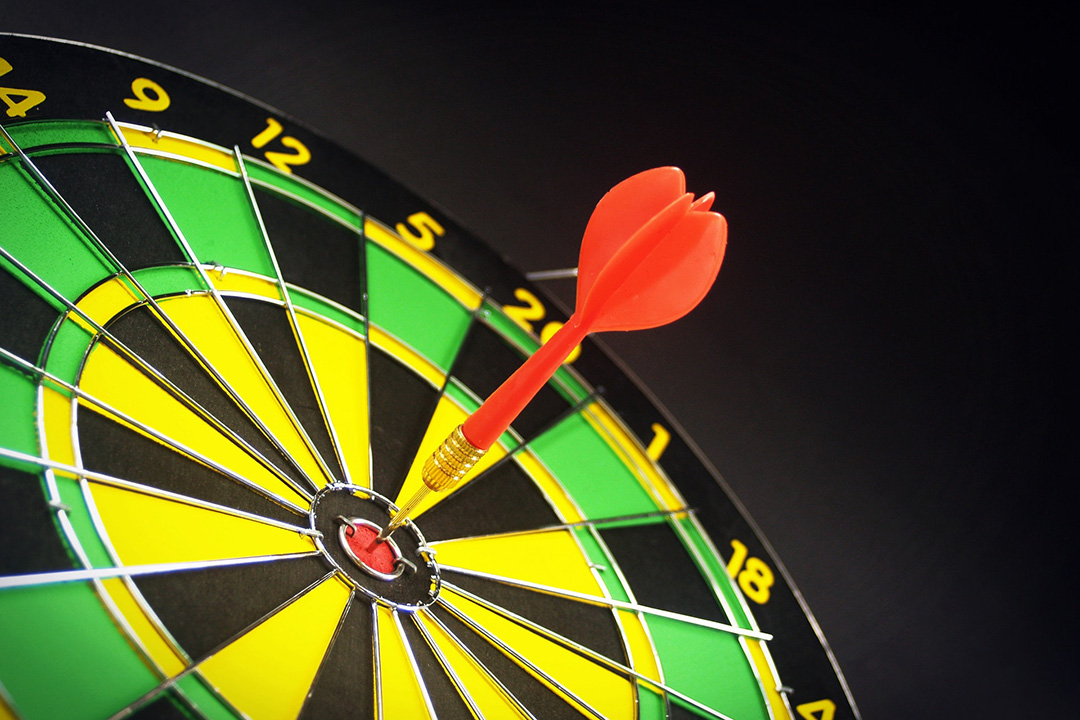 A dart hits the bull's eye on a dart board