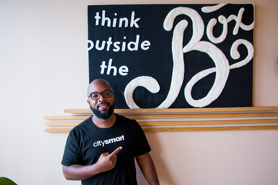 Donald Hawkins of CitySmart points to a sign that says, think outside the box
