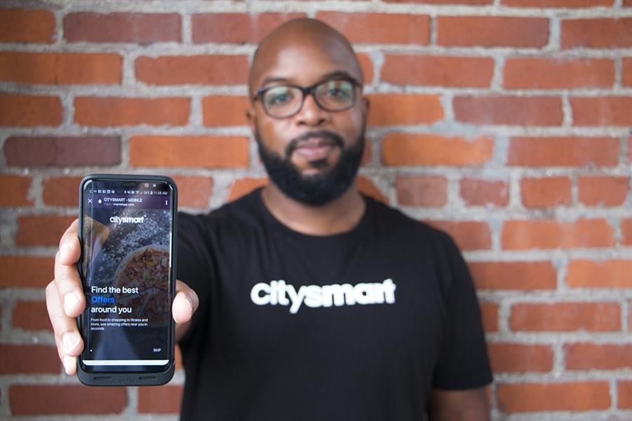 Donald Hawkins, of CitySmart, Griffin Technologies, holds a smartphone that displays his app.