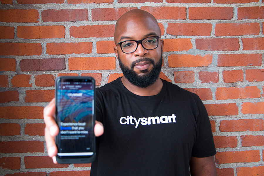 Donald Hawkins of CitySmart holds a smartphone with his app on it