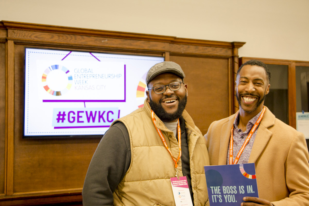 Two GEWKC attendees pose for a photo near a GEWKC sign