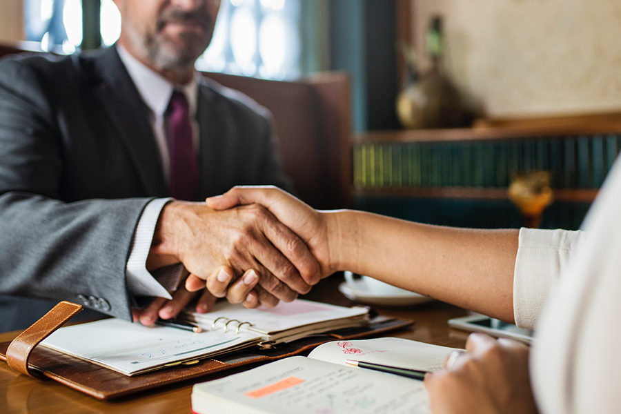 A man and a woman shake hands - How to Hire the Right Candidate for Your Kansas City Small Business