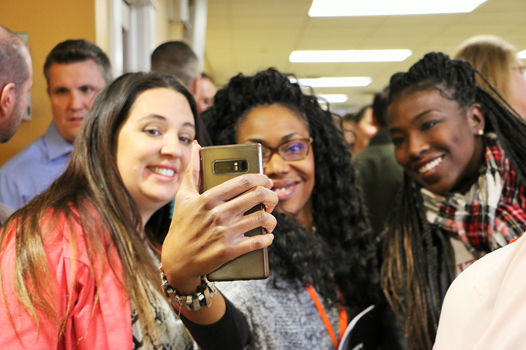 GEWKC attendees pose in front of a smartphone