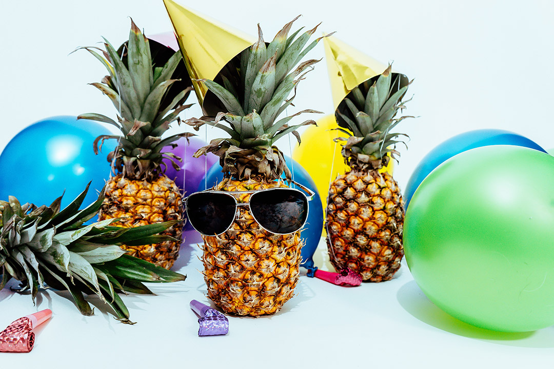 Pineapples wearing sunglasses are surrounded by balloons