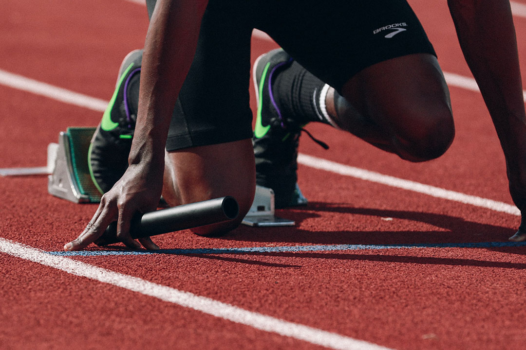 A runner gets set at the starting block on a racetrack