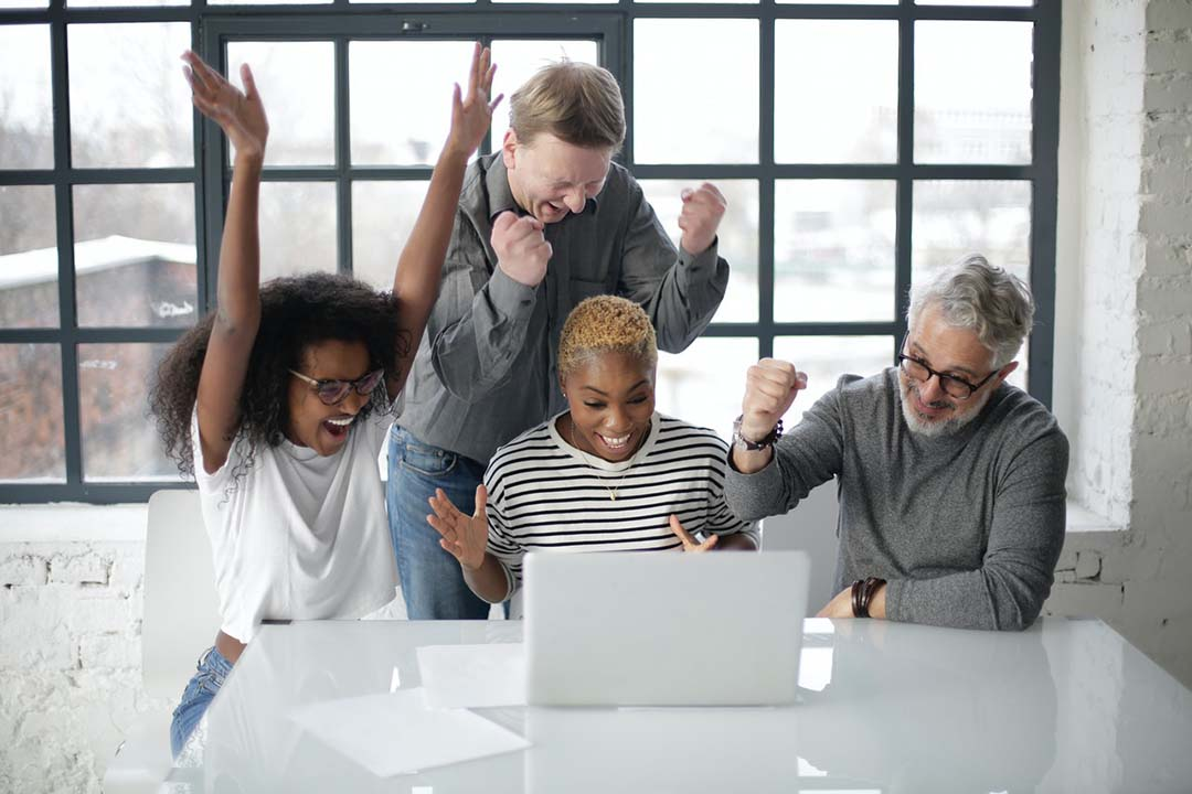 Four coworkers celebrate around a computer