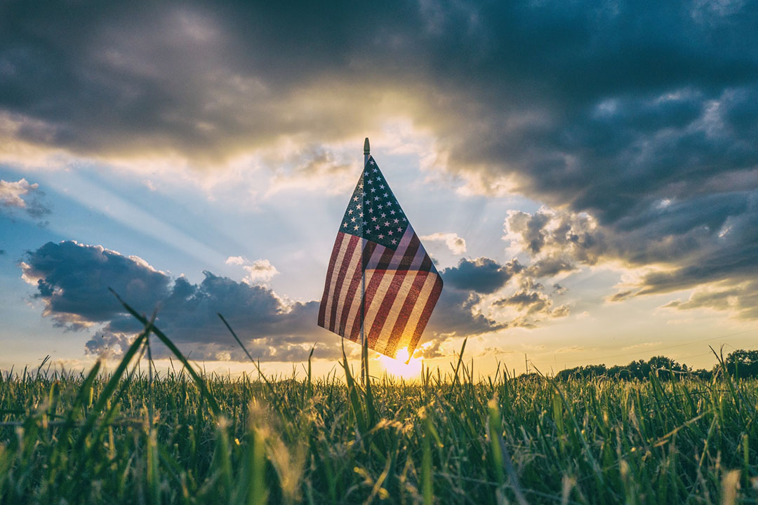 The sun's rays piece an American flag in a field