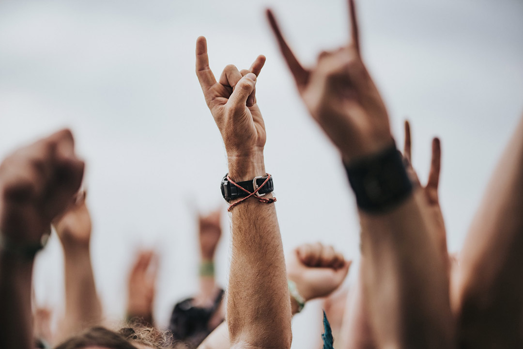 People in a crowd form the rock 'n' roll devil horns gesture with their hands