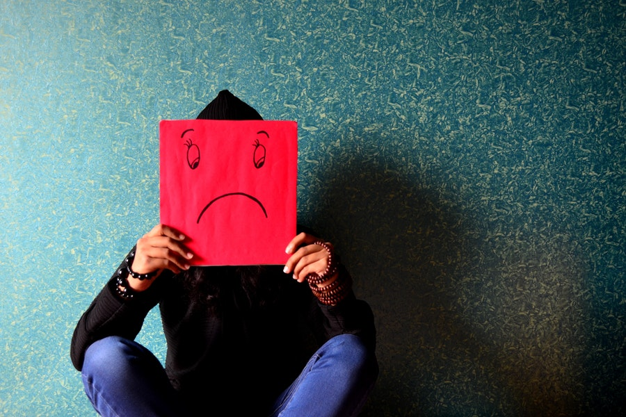 A person sits down and holds a red frowning face in front of their face