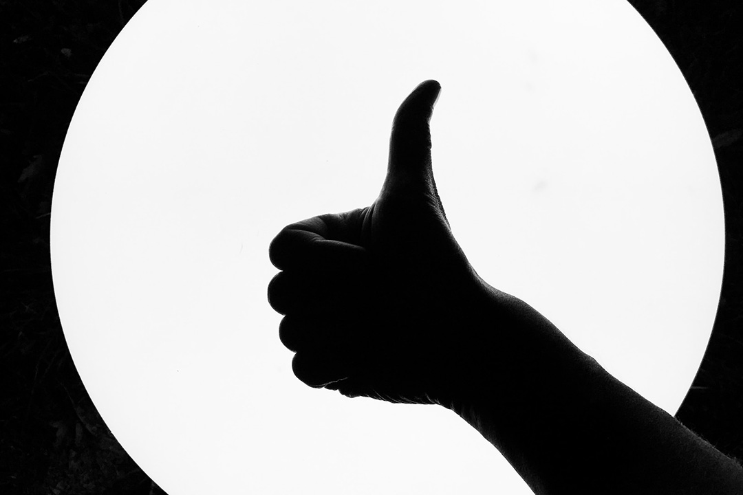 A silhouette of a thumbs up