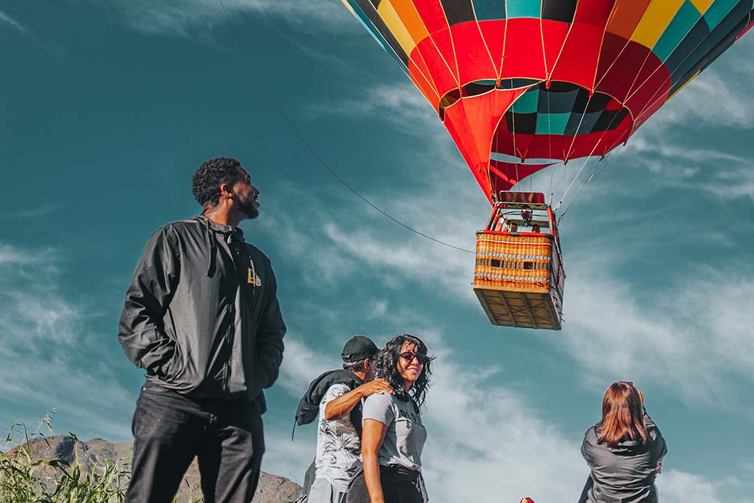 People watch a hot-air balloon rise