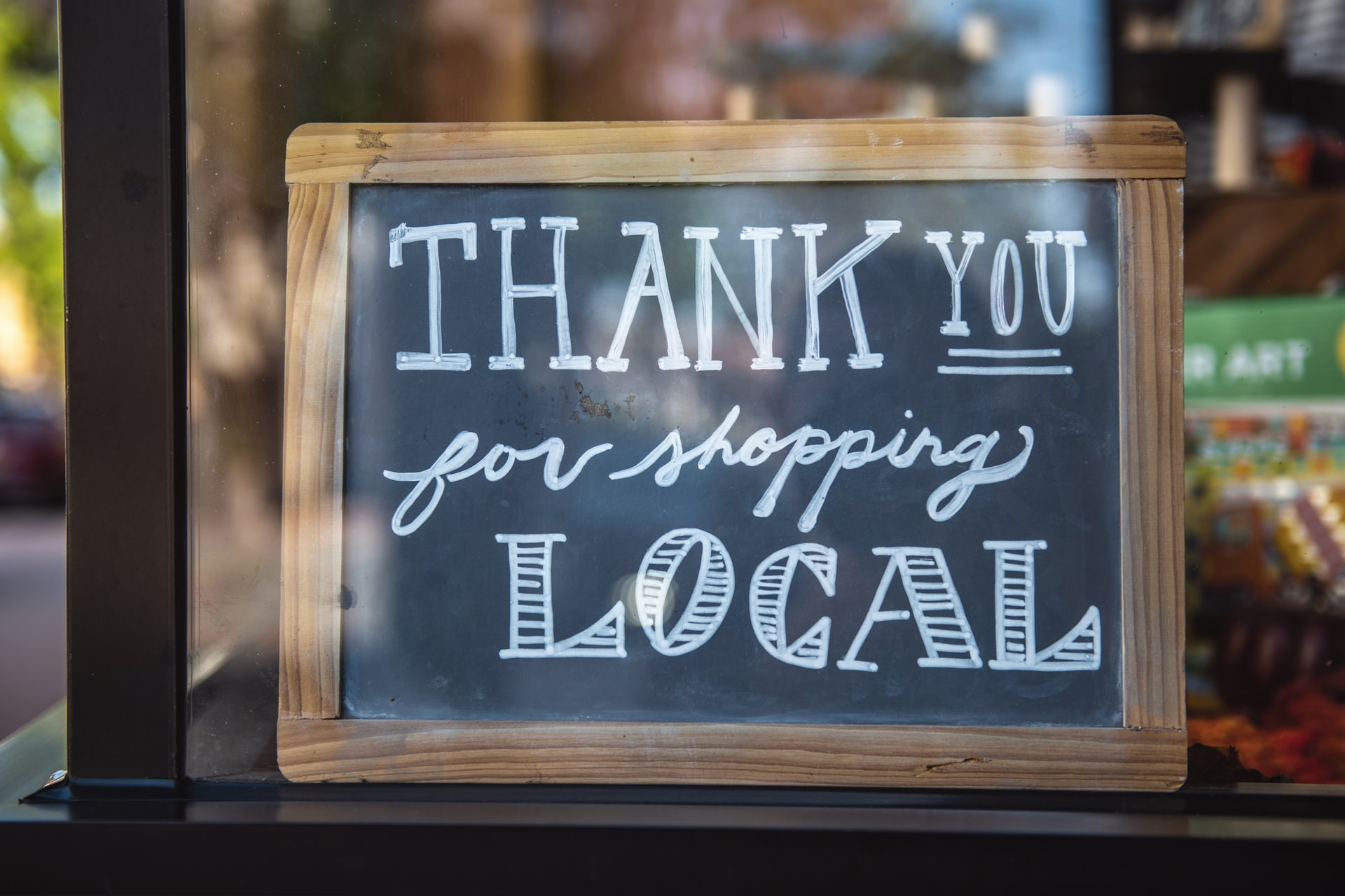A sign in a shop window shows support for small businesses