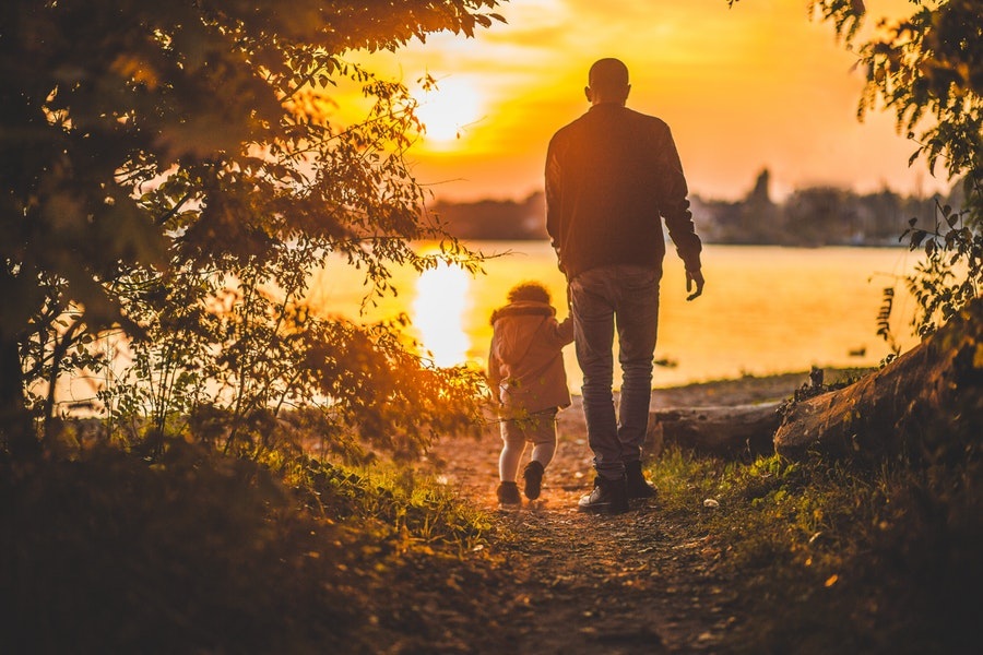 A man and a child walk toward a sunset