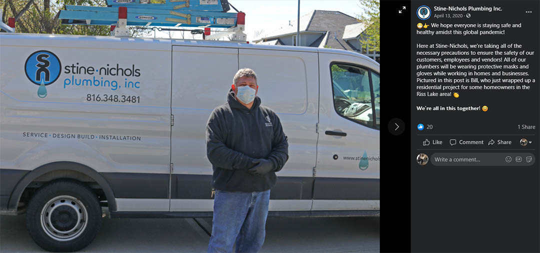 A Stine-Nichols Plumbing employee wears a mask next to a company vehicle after a job