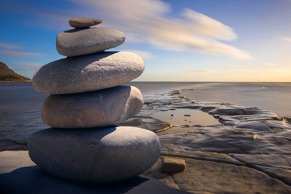 Round rocks are stacked on top of one another on a beach