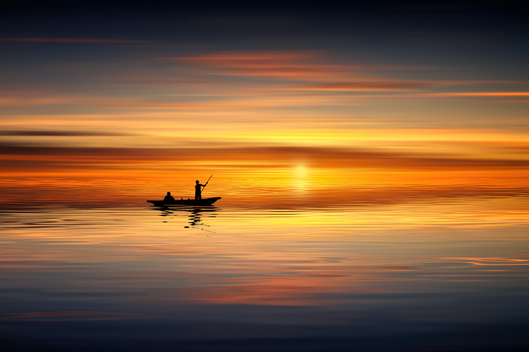a small boat floats across a large body of water at sunset
