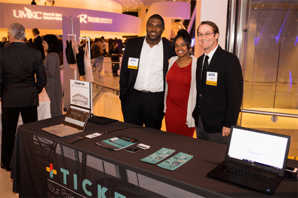 The TicketRX team poses and stands behind a booth