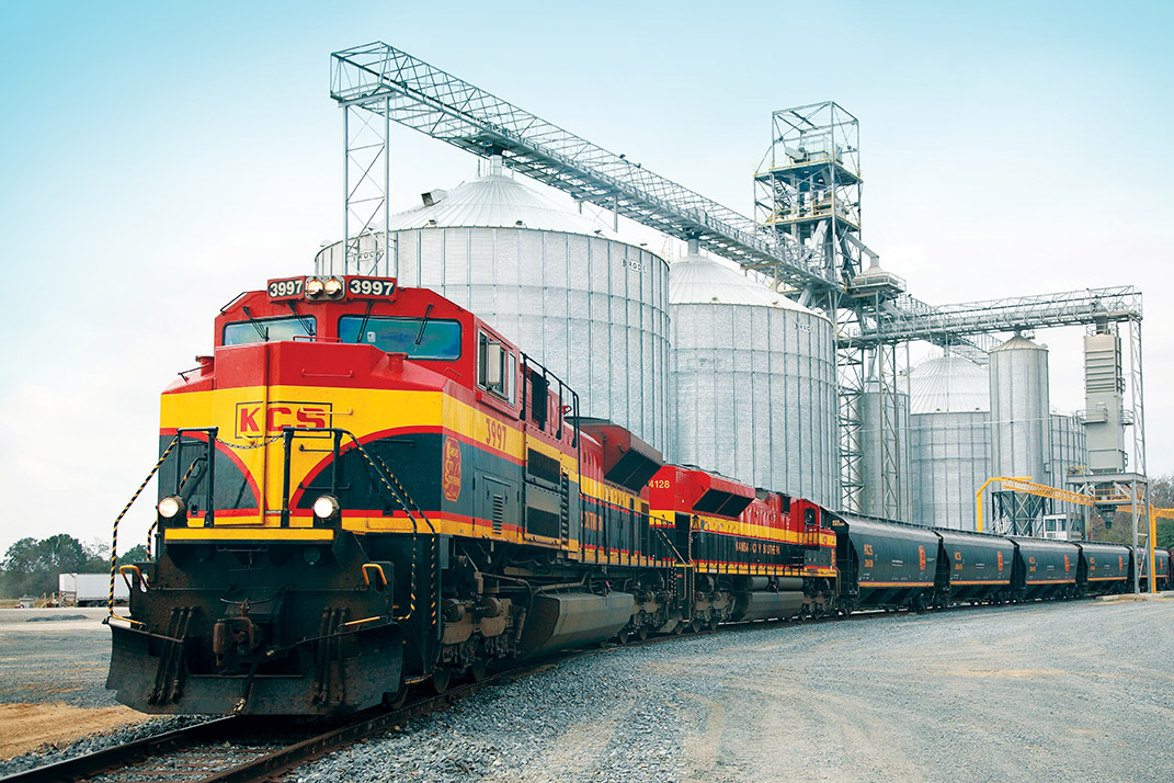 A Kansas City Southern train near a grain silo